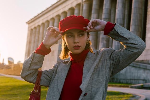 Młoda kobieta jest ubranym czerwoną nakrętkę patrzeje daleko od