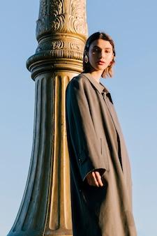 Młoda kobieta jest ubranym długiego żakieta pozycję blisko filaru przeciw niebieskiemu niebu