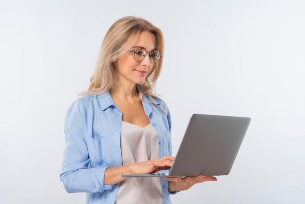 Młoda kobieta jest ubranym eyeglasses używać laptop przeciw białemu tłu