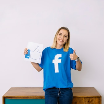 Młoda kobieta jest ubranym facebook koszulkę trzyma jak ikona pokazuje thumbup znaka