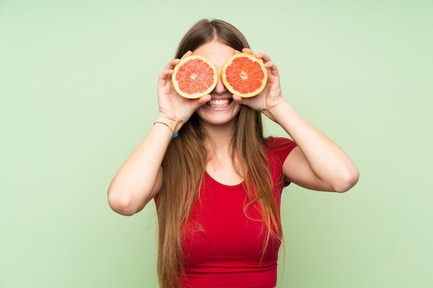 Młoda kobieta jest ubranym grapefruitowych plasterki jako szkła z długie włosy