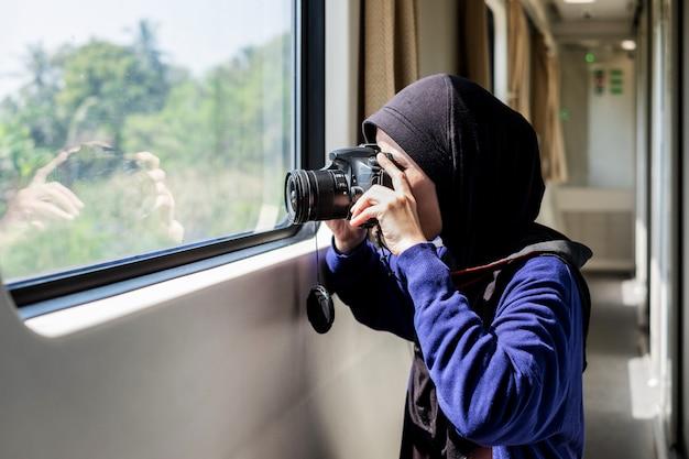 Młoda kobieta jest ubranym hijab bierze fotografię z wewnątrz pociągu.