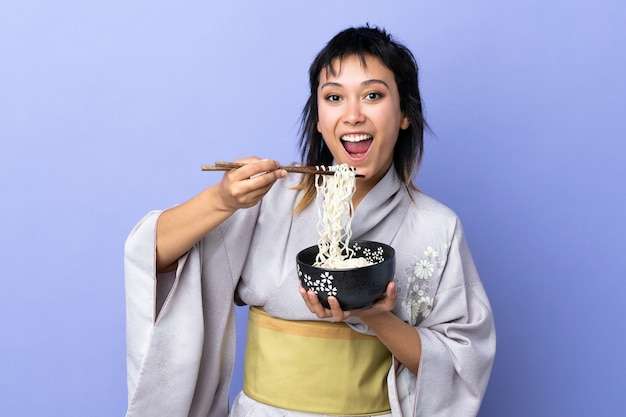 Młoda kobieta jest ubranym kimono nad odosobnionym błękitem trzyma puchar kluski z pałeczkami i je je