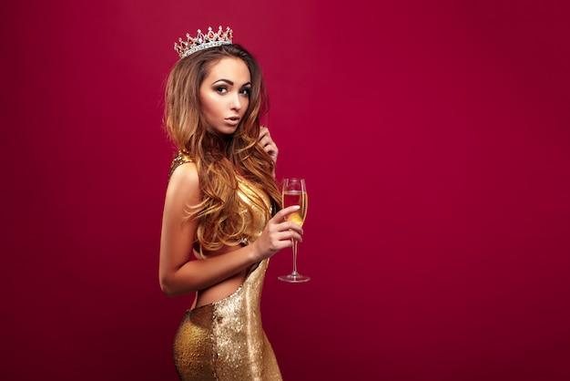 Młoda kobieta jest ubranym koronę i złotą suknię z szampanem