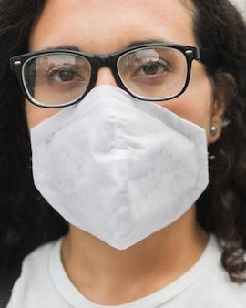 Młoda kobieta jest ubranym medycznego maskowego zakończenie