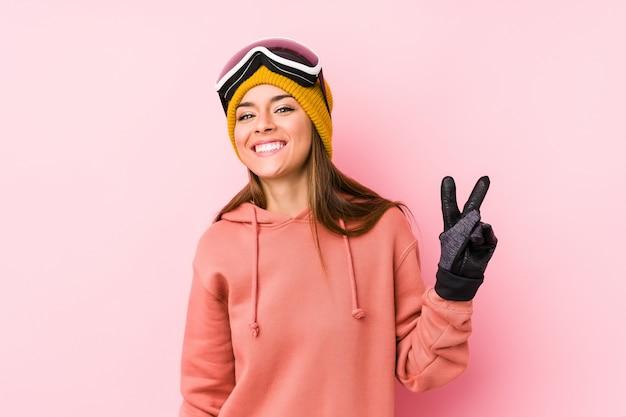 Młoda kobieta jest ubranym narciarskiego ubrania pokazuje zwycięstwo znaka i uśmiecha się szeroko