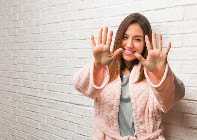 Młoda kobieta jest ubranym piżamę pokazuje liczbę dziesięć
