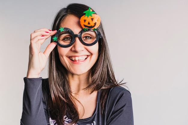 Młoda kobieta jest ubranym śmiesznych halloween szkła i ono uśmiecha się. l styl życia w pomieszczeniu. kostium szkieletowy