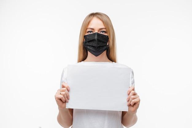 Młoda kobieta jest ubranym twarzową maskę dla ochrony trzyma pustego papier