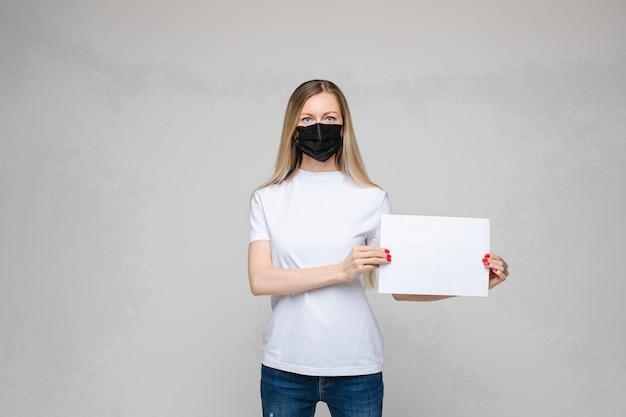 Młoda kobieta jest ubranym twarzy maskę trzyma puste miejsce znaka