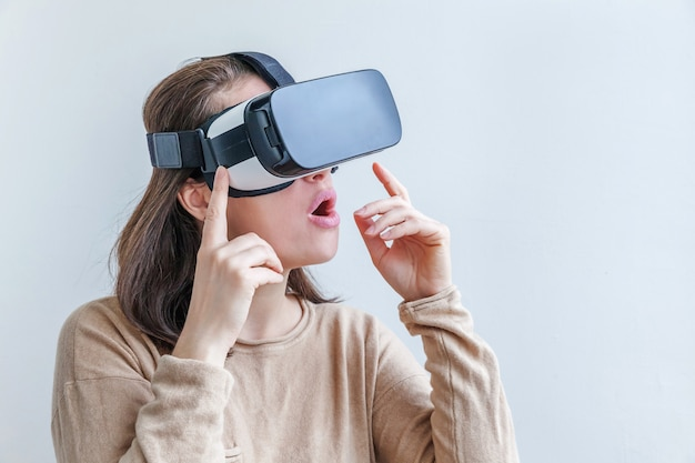 Młoda kobieta jest ubranym używać rzeczywistości wirtualnej vr szkieł hełma słuchawki na białym tle. technologia, symulacja, hi-tech, koncepcja gier wideo.