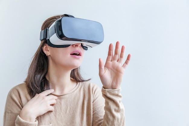 Młoda kobieta jest ubranym używać rzeczywistości wirtualnej vr szkieł hełma słuchawki na białym tle.