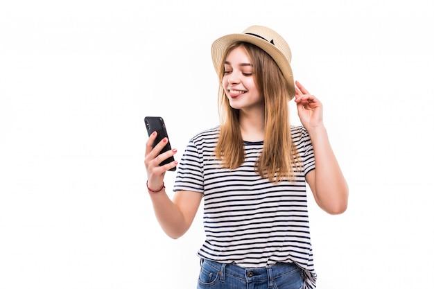Młoda kobieta jest ubranym w słomianym kapeluszu i okularach przeciwsłonecznych robi rozmowie wideo