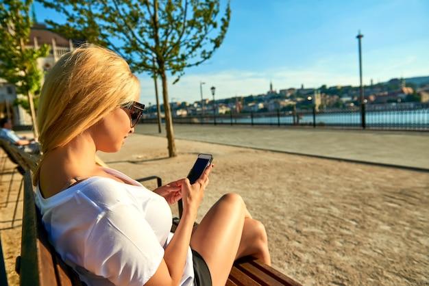 Młoda kobieta jest usytuowanym na ławce i używa jej telefon