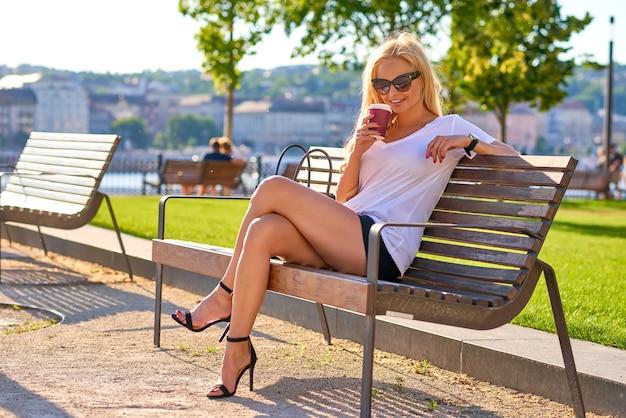 Młoda kobieta jest usytuowanym na ławce z kawą