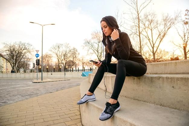 Młoda kobieta jest usytuowanym na schodkach
