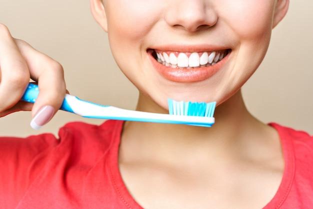 Młoda kobieta jest zaangażowana w czyszczenie zębów