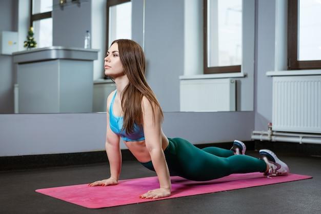 Młoda kobieta jest zaangażowana w rozciąganie na siłowni na macie w odzieży sportowej