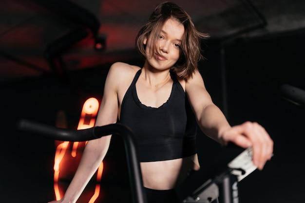 Młoda kobieta jest zaangażowana w siłownię, ćwicząc na symulatorze