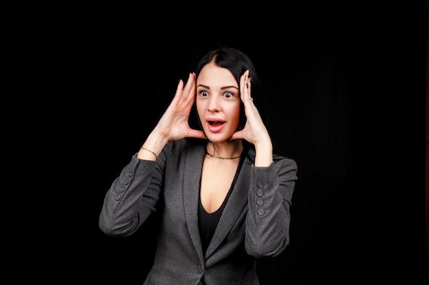 Młoda kobieta jest zaskoczona. dziewczyna nosi zwykłą szarą kurtkę na czarnej przestrzeni. zła kobieta, ręce po bokach.