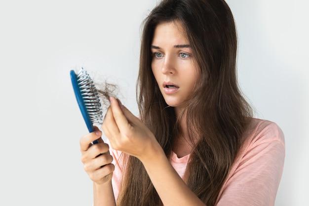 Młoda kobieta jest zdenerwowana z powodu wypadania włosów