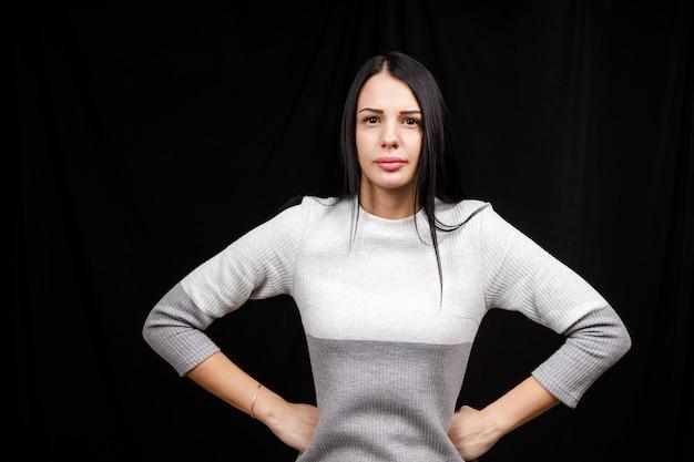 Młoda kobieta jest zła. dziewczyna nosi dorywczo słodsze na czarnym tle. zła kobieta, ręce po bokach.