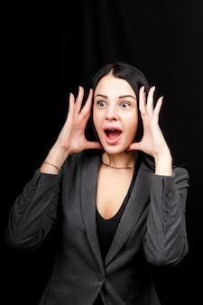 Młoda kobieta jest zła. dziewczyna nosi zwykłą szarą kurtkę na czarnej przestrzeni. zła kobieta, ręce po bokach.