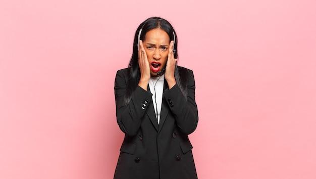 Młoda kobieta jest zszokowana i przerażona, wygląda na przerażoną z otwartymi ustami i dłońmi na policzkach
