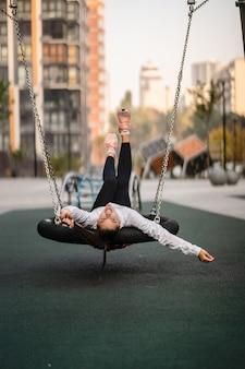 Młoda kobieta jeździ na huśtawce. dziewczyna odpoczywa na placu zabaw.