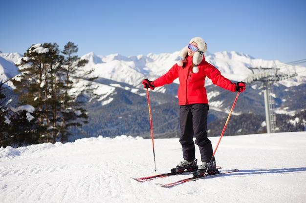 Młoda kobieta jeździ na nartach w ośrodku narciarskim