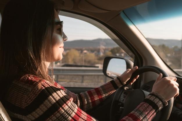 Młoda kobieta jeździ samochodem.
