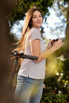 Młoda kobieta jeździ skuterem elektrycznym w parku
