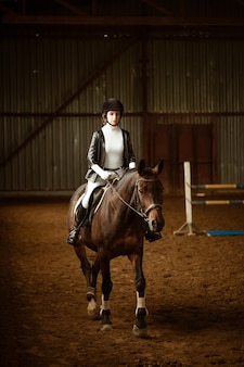 Młoda kobieta jeździec na koniu ujeżdżeniowym abstrakcyjne ujęcie konia podczas zawodów ładna dziewczyna dżokej si...