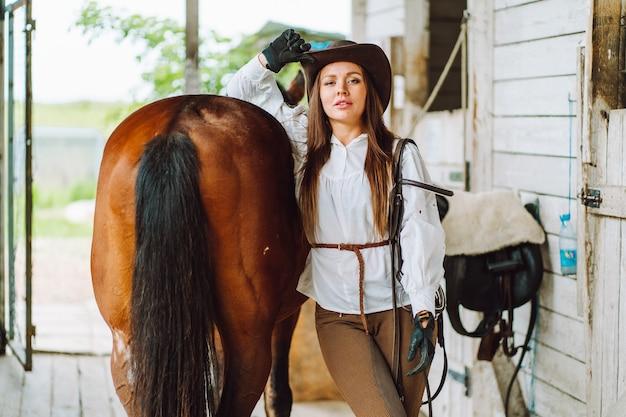 Młoda kobieta jeździec ubrana w białą koszulę i kapelusz z brązowym koniem na straganie, portret.