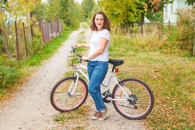 Młoda kobieta jeździecki bicykl w lata miasta parku outdoors