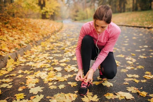Młoda kobieta jogger siedzi w pozycji oddziału i zawiązuje sznurowadła na swoich butach. słucha muzyki przez słuchawki. młoda kobieta jest skoncentrowana.