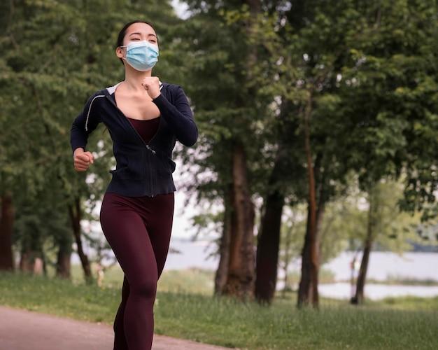 Młoda kobieta jogging z medyczną maską dalej