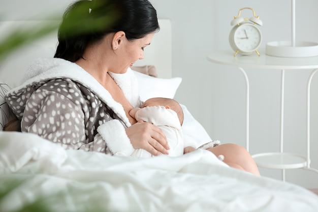 Młoda kobieta karmi piersią swoje dziecko w domu