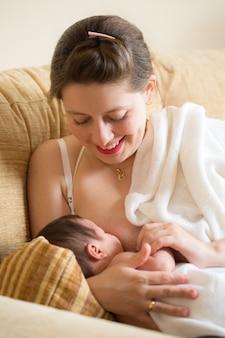 Młoda kobieta karmi piersią swojego noworodka