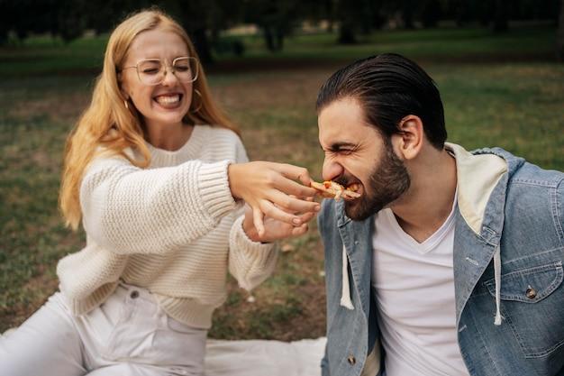 Młoda kobieta karmi pizzę swojemu chłopakowi