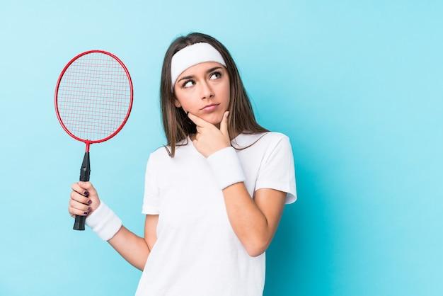 Młoda kobieta kaukaska gra w badmintona na białym tle patrząc z ukosa z wyrazem wątpliwości i sceptycyzmu.