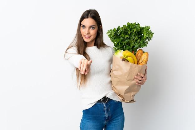 Młoda kobieta kaukaska kupuje jedzenie na białym, wskazując przód z happy wypowiedzi