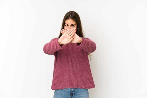 Młoda kobieta kaukaska na białym tle na białej przestrzeni robi gest odmowy