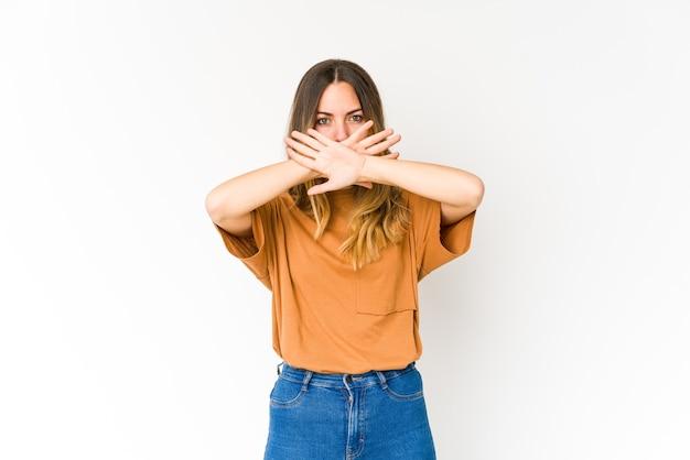Młoda kobieta kaukaska na białym tle na białej ścianie robi gest odmowy