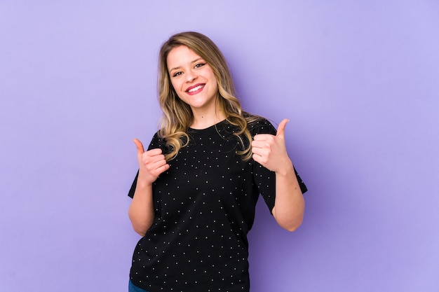 Młoda kobieta kaukaska na białym tle na fioletowym tle, podnosząc kciuki do góry, uśmiechnięta i pewna siebie.