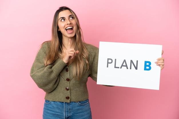 Młoda kobieta kaukaska na białym tle na różowym tle trzymając tabliczkę z komunikatem plan b i myślenia