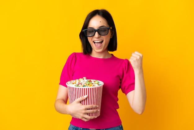 Młoda kobieta kaukaska na białym tle na żółtej ścianie w okularach 3d i trzyma duże wiadro popcorns