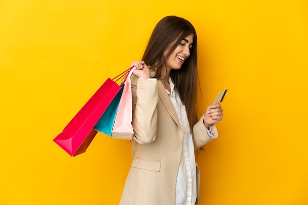 Młoda Kobieta Kaukaska Na Białym Tle Na żółtym Tle, Trzymając Torby Na Zakupy I Kartę Kredytową Premium Zdjęcia