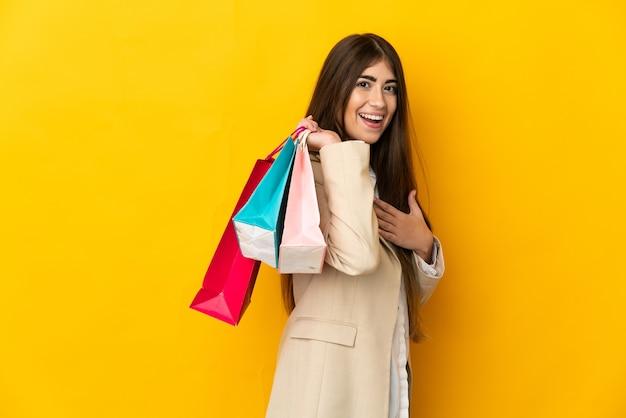 Młoda kobieta kaukaska na białym tle na żółtym tle trzymając torby na zakupy i uśmiechnięte