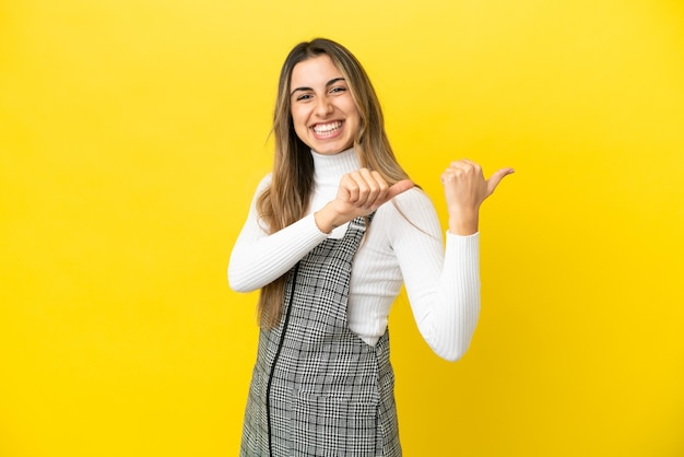 Młoda kobieta kaukaska na białym tle na żółtym tle, wskazując w bok, aby przedstawić produkt